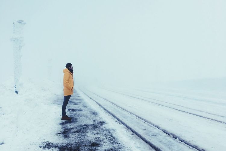 Side View Of Man Standing On Snow Covered Road