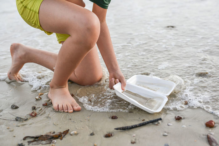 Barefoot Beach Childhood Day Garbage Garbage Bin Low Section Nature Nature Conservation One Person Outdoors People Real People Sand Sand Pail And Shovel Sea Vacations Water