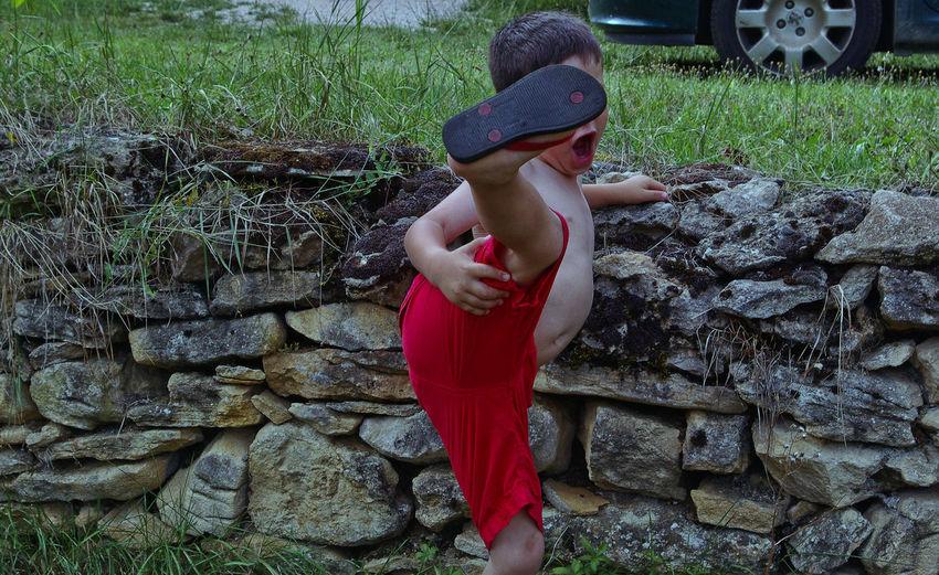Boy kicking by stone wall on field