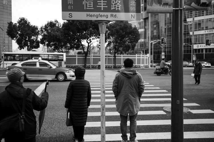 City Car Motor Vehicle Transportation Mode Of Transportation Street Rear View Sign Road Land Vehicle Real People Crossing Men City Life Tree Architecture Crosswalk Walking Road Marking Road Sign City Street Outdoors Streetphotography Blackandwhite LEICA M