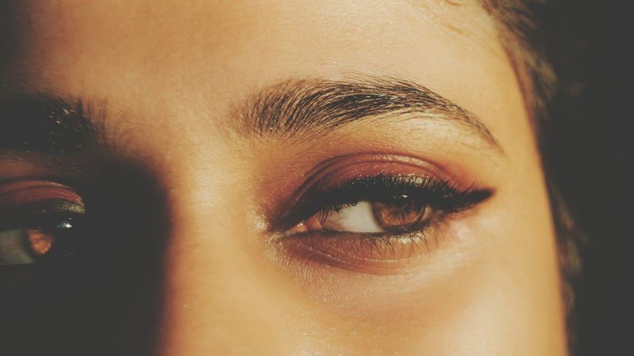 Cropped image of young woman with eye make-up looking away