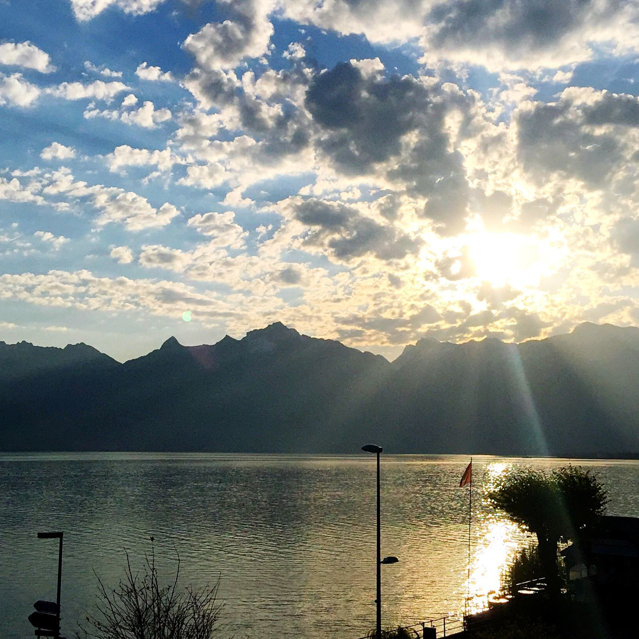 Sunlight Falling On Silhouette Mountains And Lake