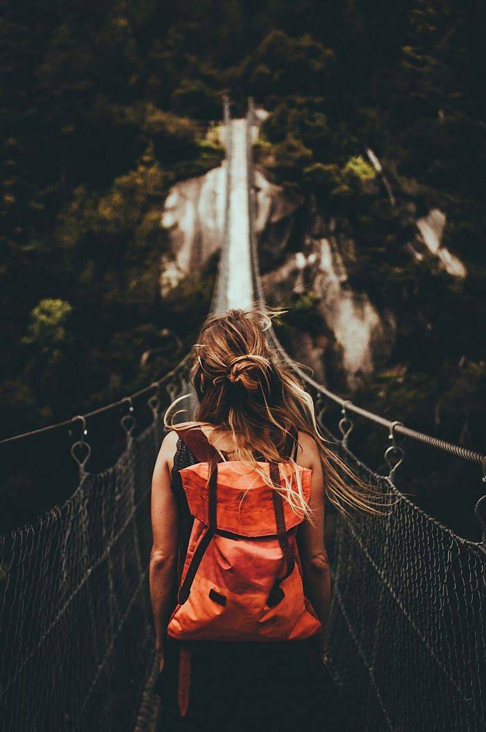 Rear view of woman standing on footbridge at forest
