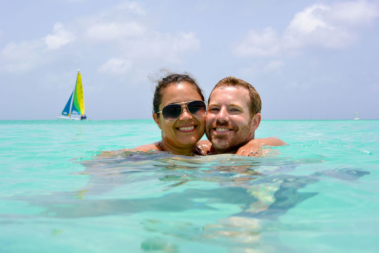 Portrait of smiling couple swimming in sea
