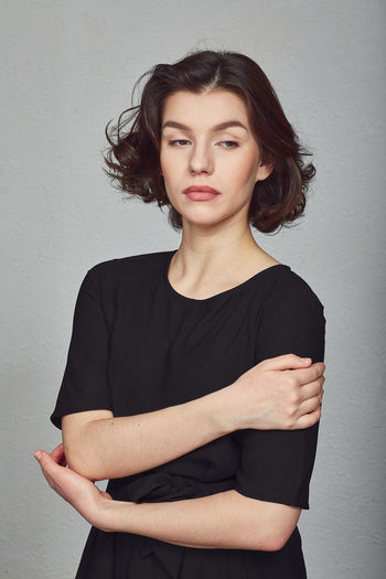 Portrait of a beautiful young woman standing against wall