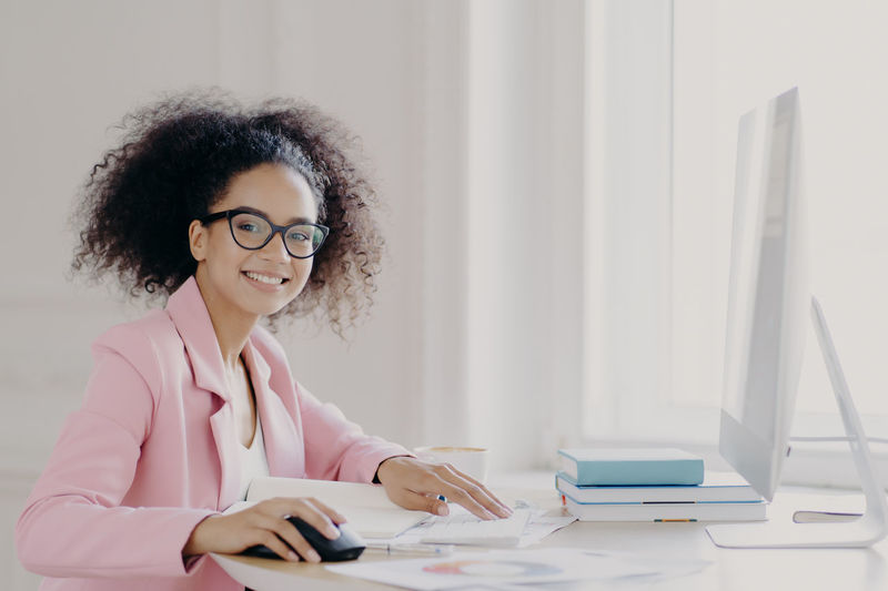 Portrait of smiling businesswoman working on computer
