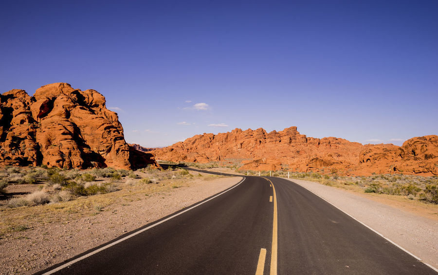 Asphalt Beauty In Nature Blue Clear Sky Day Desert Highway Landscape Mountain Mountain Road Nature No People Outdoors Road Rock - Object Scenics The Way Forward Travel Winding Road