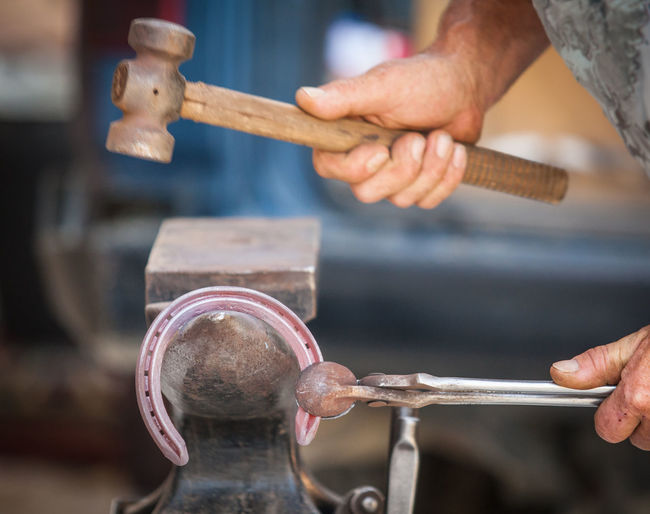 Blacksmith hands shaping horseshoe with hammer in workshop