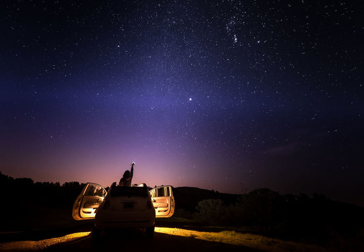 Rear view of woman in car against star field