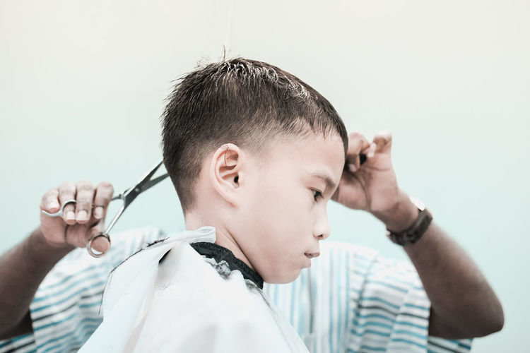 Barber cutting boy hair at salon