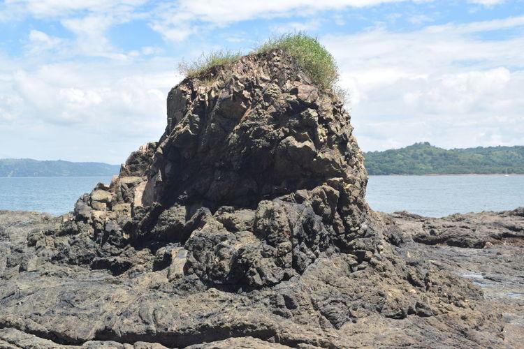 Rock in sea against sky