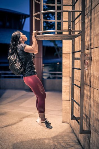 Side view of woman hanging on metal