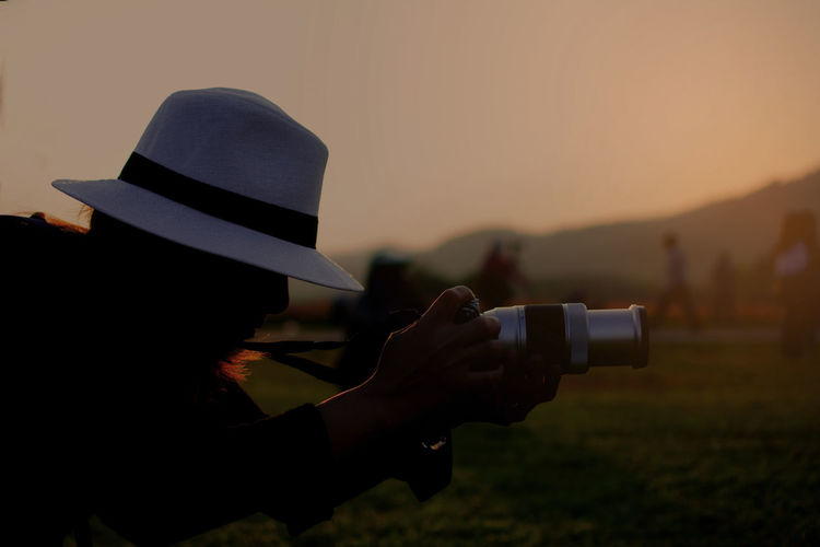 Silhouette of woman photographer during sunset, Asian tourist take the photo Hat Real People Sunset One Person Holding Photography Themes Sky Activity Leisure Activity Photographing Lifestyles Technology Camera - Photographic Equipment Nature Digital Camera Occupation Photographer Headshot Silhouette Woman Tourist Relaxing Freestyle Asian  Job Working Travel Taking Photos Landscape Digital Camera