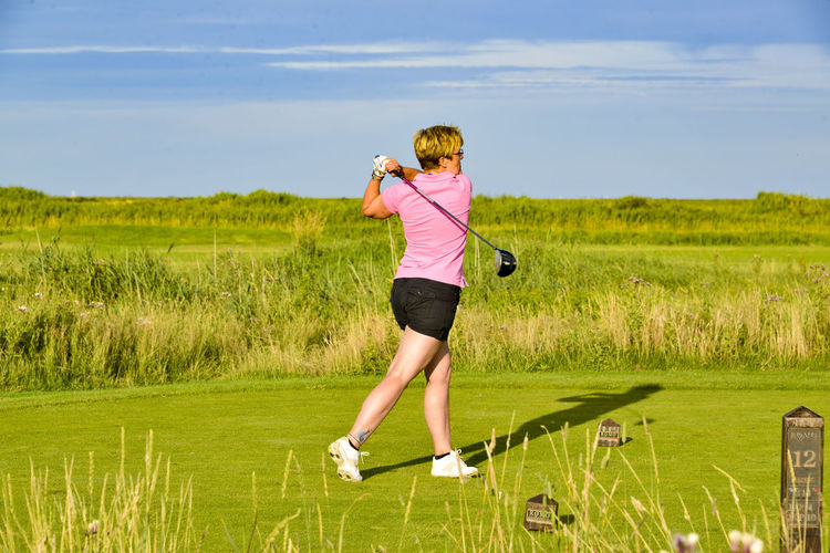Full length of woman playing golf against sky