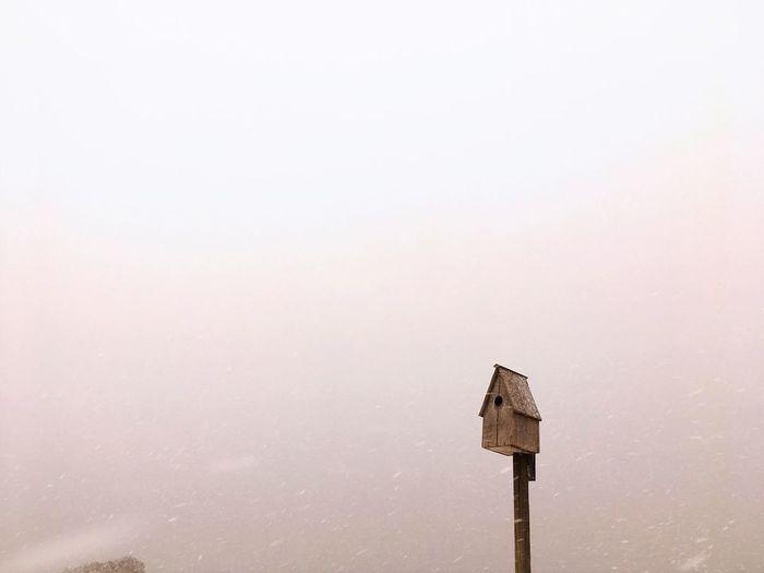 Bird house against cloud sky