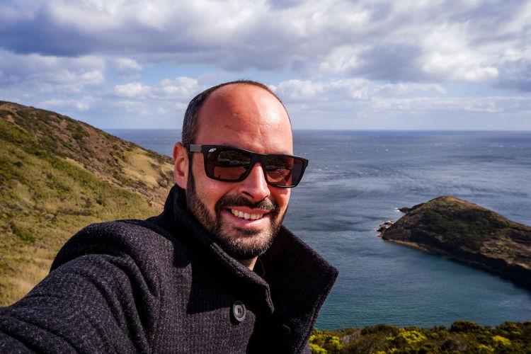 Portrait of smiling man against sea ad sky