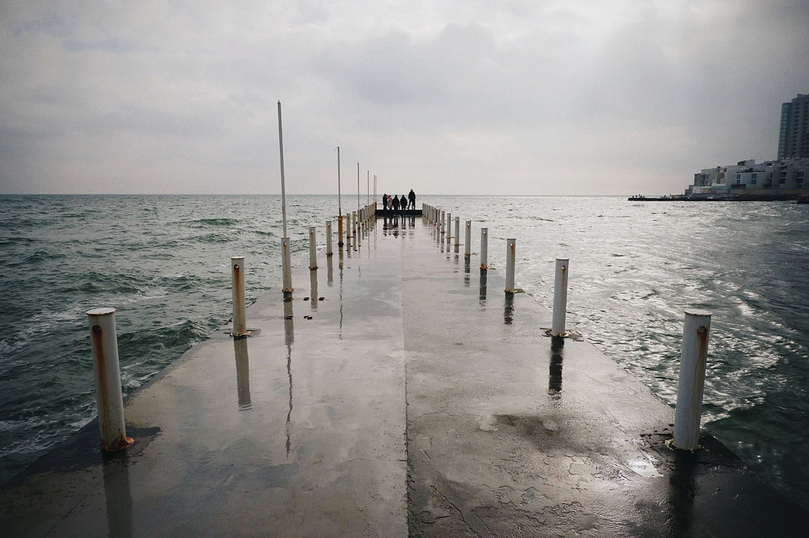 water, sea, sky, horizon, cloud - sky, pier, post, horizon over water, nature, scenics - nature, beauty in nature, tranquility, direction, architecture, built structure, tranquil scene, day, wood - material, beach, wooden post, no people, outdoors, diminishing perspective