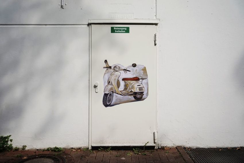 Scooter Graffiti Art Emergency Exit Wall - Building Feature Communication Text Sign Representation Safety No People Day Architecture Built Structure Security Western Script Protection White Color Door Entrance Outdoors Closed Information