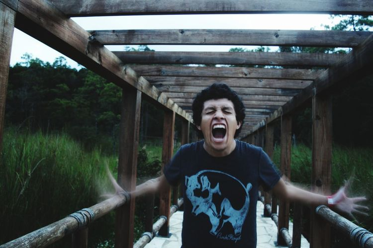 Young man shouting while standing on footbridge