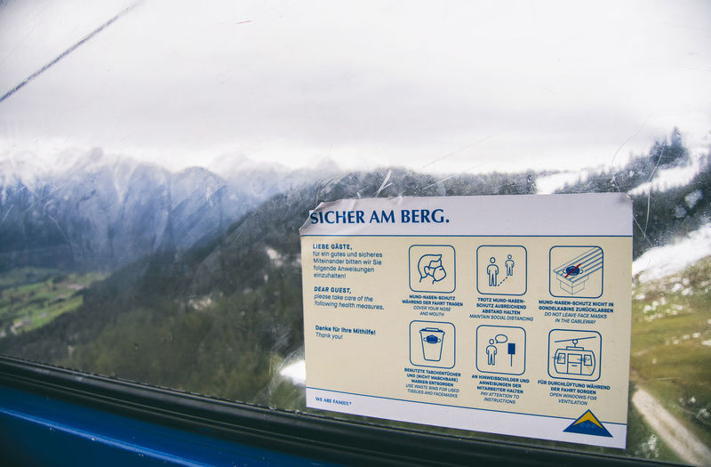 Information sign on snowcapped mountains seen through window