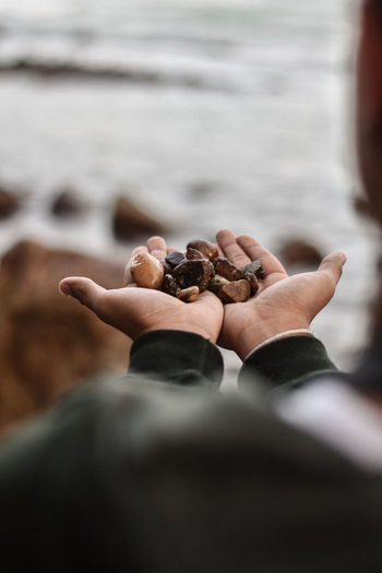 Close-up of hand holding rock in sea