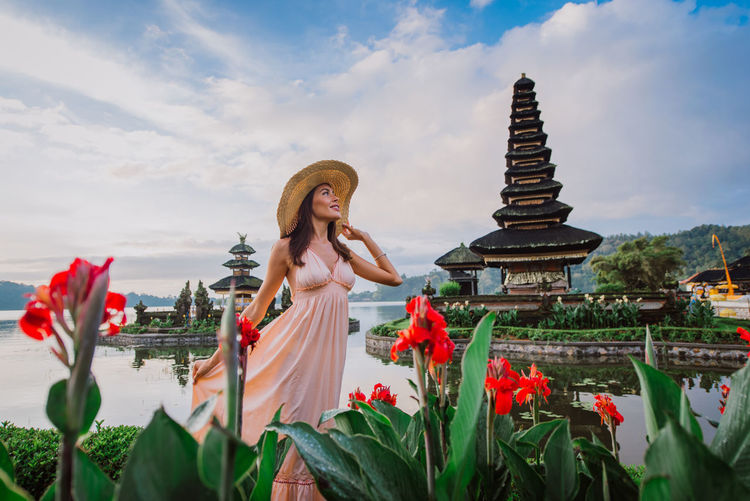 Woman standing at pura ulu danau temple against sky during sunrise