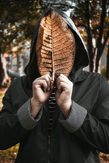 Man covering face with leaf during autumn