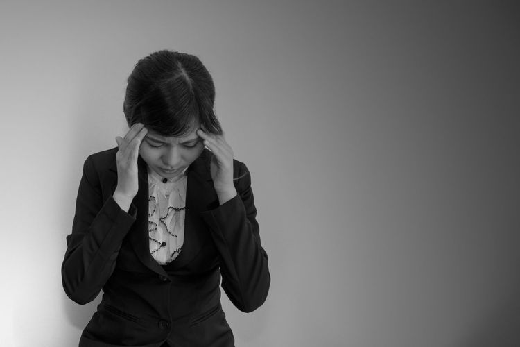 Businesswoman With Headache Standing Against Wall