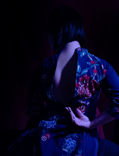 Rear view of woman standing in darkroom