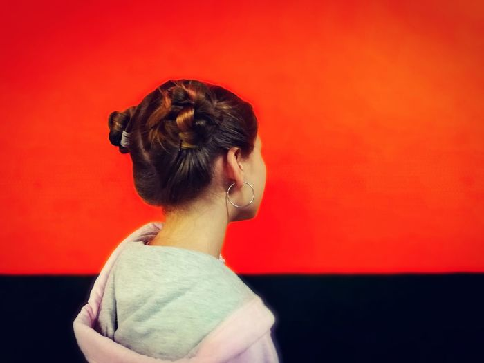Rear view of woman standing against red background