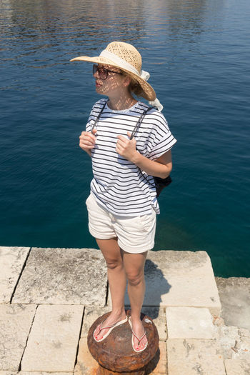 Full length of woman looking away while standing by sea