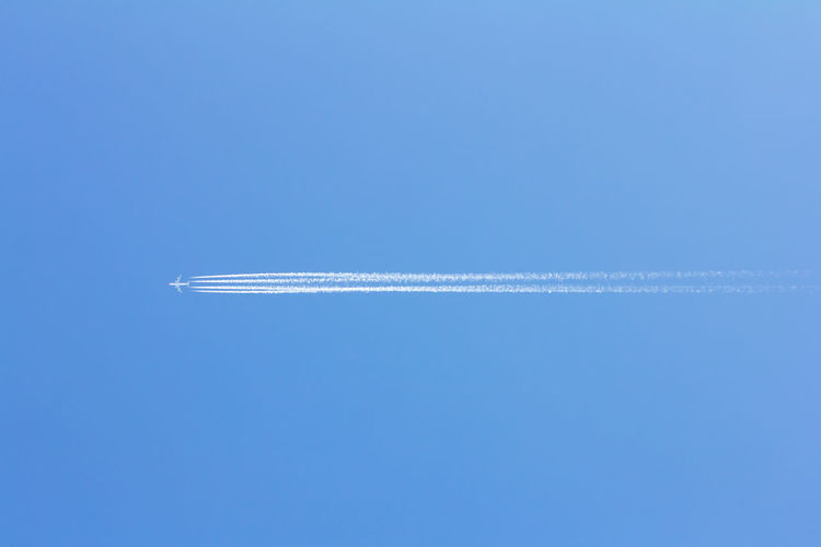 Plane flying overhead through blue sky, with vapor trail behind Holidays Air Vehicle Airplane Blue Cloud - Sky Copy Space Day Flying Leaving Low Angle View Mid-air Mode Of Transportation Motion No People on the move Outdoors Parallel Plane Sky Smoke - Physical Structure Summer Trail Transportation Vacation Vapor Trail