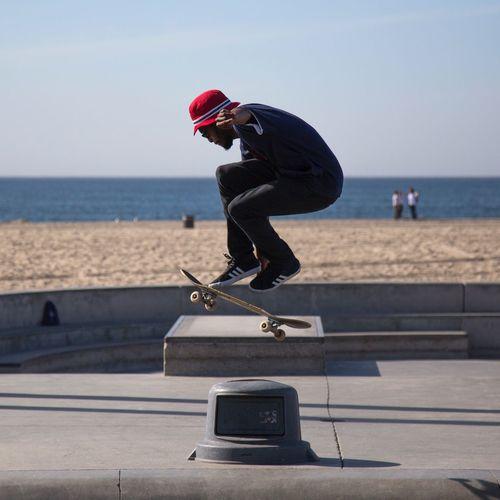 Man skateboarding on skateboard by sea against clear sky