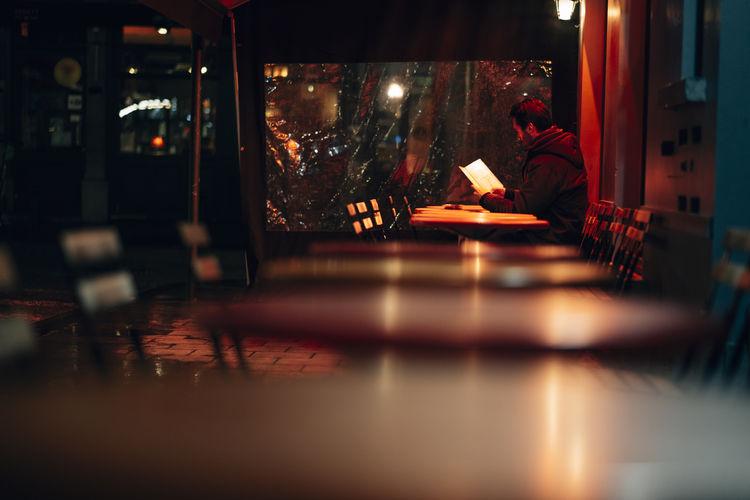 Man sitting on table at illuminated restaurant