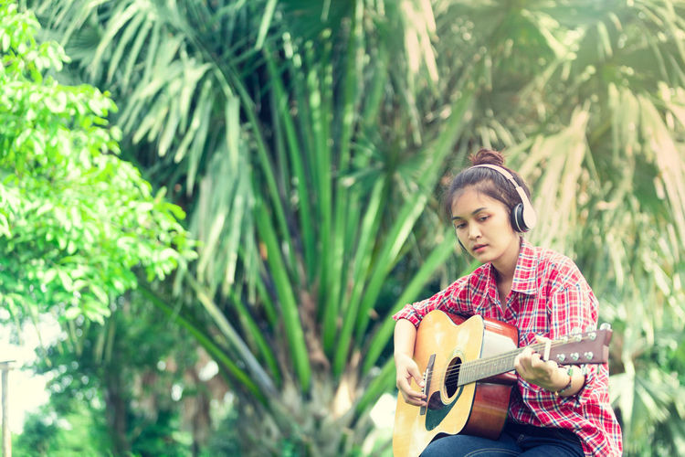 Headphones Holiday Arts Culture And Entertainment Beautiful Woman Casual Clothing Day Garden Guitar Holding Leisure Activity Model Asian Music Musical Equipment Musical Instrument Musician Nature One Person Outdoors Plant Playing Plucking An Instrument String Instrument Tree Young Adult Young Women