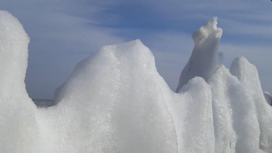 Close-up of snow against sky during winter