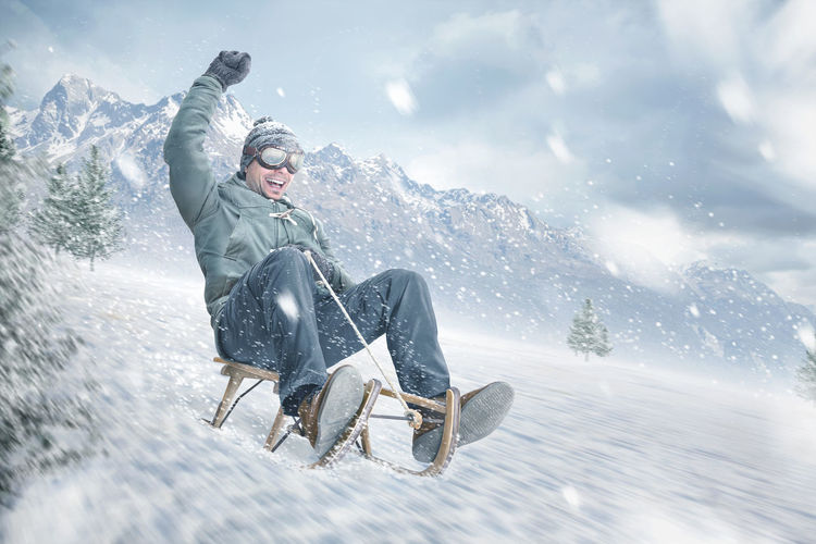 Low angle view of cheerful man tobogganing on snowcapped mountain