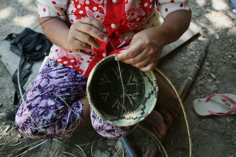 High angle view of woman weaving basket