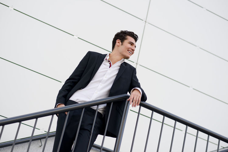 Low angle view of businessman standing by railing against wall
