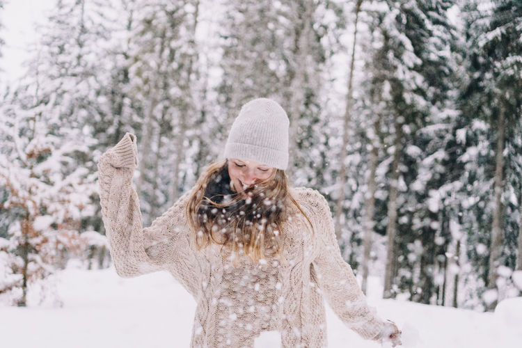 Woman wearing hat against trees in forest during winter