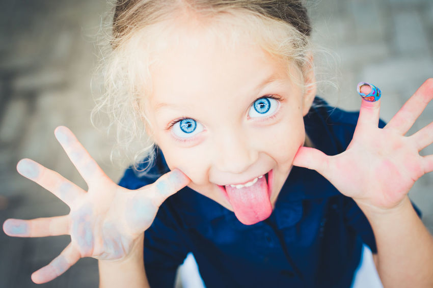 Tongue Out Blue Cheeky Child Childhood Day Eyes Focus On Foreground Happiness Headshot Human Face Human Hand Little Looking At Camera One Person Outdoors Portrait Smiling