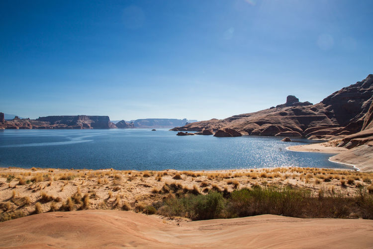 Morning view of Lake Powell near Gunsight Ridge near Page, Arizona. Sky Water Mountain Sea Beauty In Nature Scenics - Nature Beach Tranquility Nature No People Rock Sand Copy Space Tranquil Scene Clear Sky Blue Outdoors Lake Powel Desert Arizona Utah Reservoir Boating Day