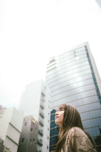 Low angle view of woman standing against buildings