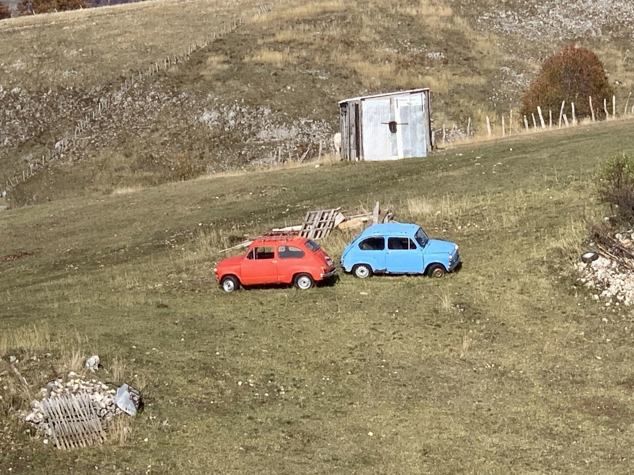 HIGH ANGLE VIEW OF ABANDONED CARS ON ROAD