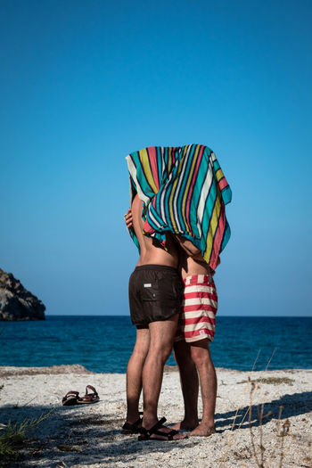 Gay men under towel romancing at beach against clear sky