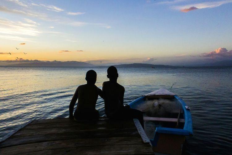 Silhouette men sitting on shore against sky during sunset