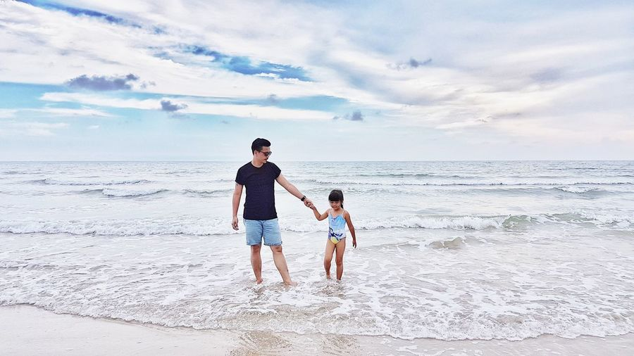 Full length of father and daughter standing on beach against sky