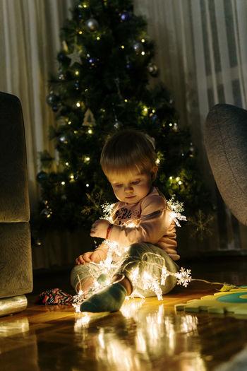 Girl looking at illuminated christmas tree at home