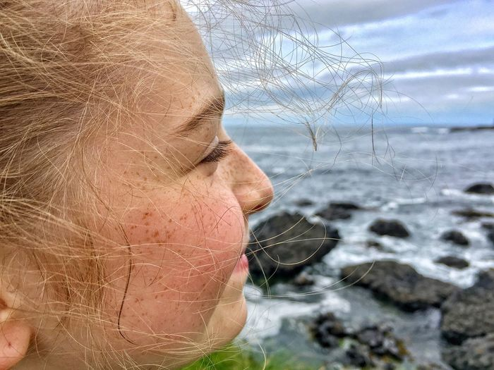 Close-up of girl with sea in background