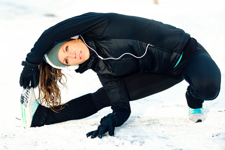 Woman Listening Music While Exercising On Snowy Field